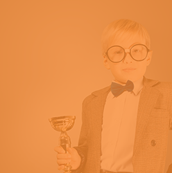 Boy with glasses holding trophy